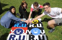 Representatives from each of the four network high schools holding the You R U logo designed in their school colours.